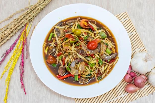 Papajasalade in een wit bord wordt op tafel gezet en knoflookrijst, uien en rijstoren worden eromheen geplaatst.