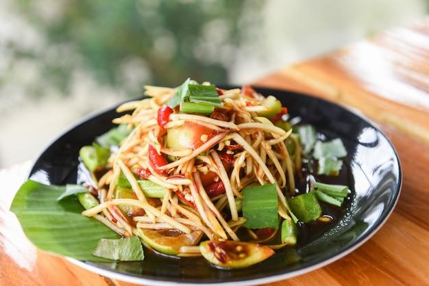Papajasalade op eettafel groen kruidig thais voedsel van de papajasalade
