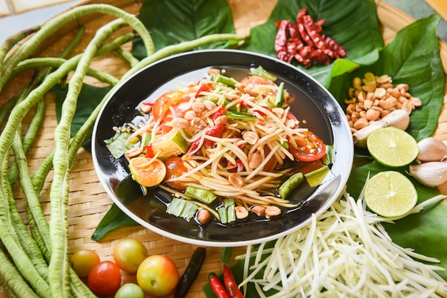 Papajasalade op houten eettafel wordt gediend die