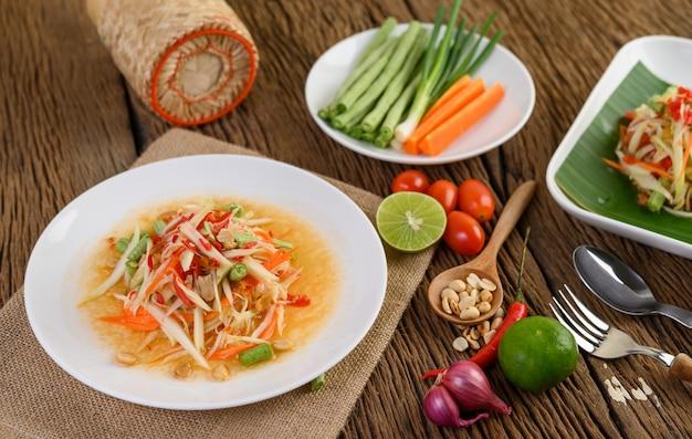 Papajasalade (som tum thai) op een witte plaat op een houten lijst.