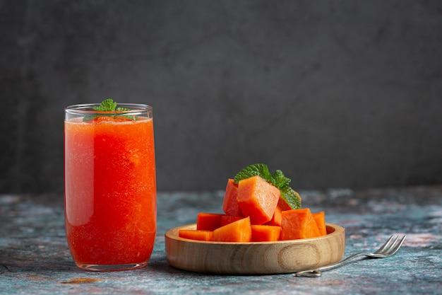 Papajasap serveren met vers gesneden papaja