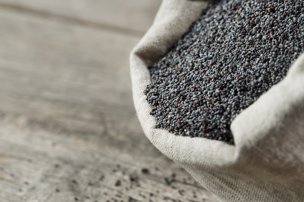 Papaverzaden in een jutezak. de smakelijke en nuttige zaden rijk aan eiwitten en oliën.