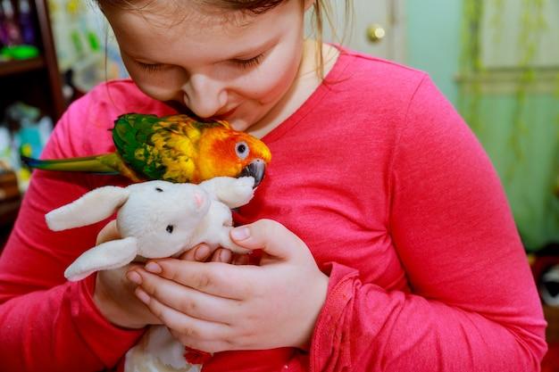 Papegaaivogel op jonge meisje hand milieu mens en natuur concept glimlachend spelen met haar vogel huisdier.