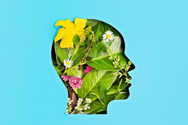 Papercut hoofd met groene bladeren en bloemen