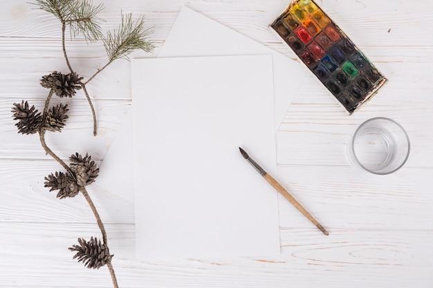Papers in de buurt van glas, penseel, takjes en waterkleuren