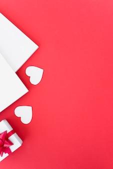 Papers in de buurt van ornament harten en geschenkdoos