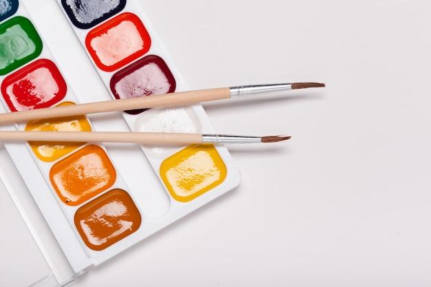 Papier, aquarellen, kwast en sommige kunstspullen close-up bovenaanzicht