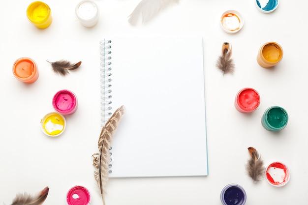 Papier, aquarellen, kwast en wat kunstspullen op een tafelblad