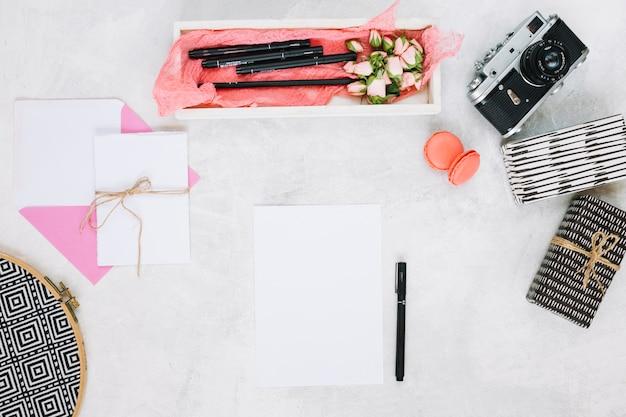 Papier blad en pen in de buurt van geschenken en camera