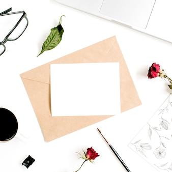 Papier blanco, ambachtelijke envelop, rode rozen, laptop, koffie op wit oppervlak