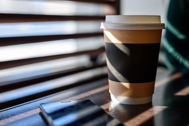 Papier en karton beker met koffie, cappuccino, latte, thee op een houten tafel in het café in fel zonlicht vanuit het raam in het voorjaar