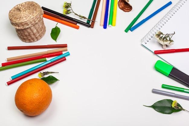 Papier en kleurrijke viltstiften op de witte tafel