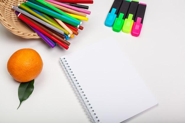 Papier en kleurrijke viltstiften op witte tafel