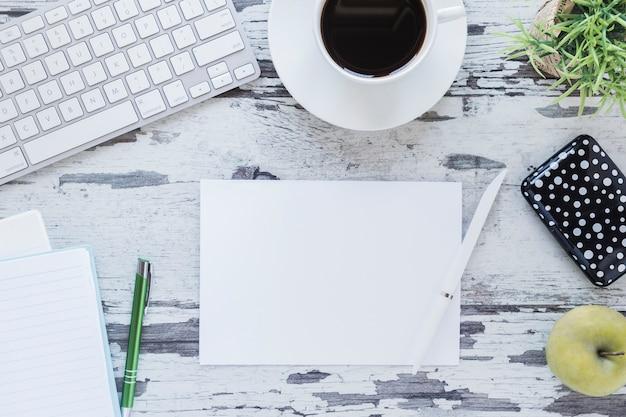 Papier en potlood in de buurt van toetsenbord en koffiekopje