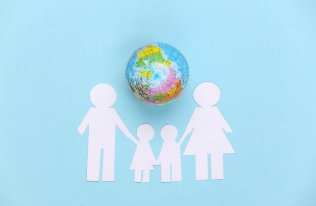 Papier familie samen met globe op blauw. concept van ecologie, bevolking, familie, dag van de aarde. wereld ons huis