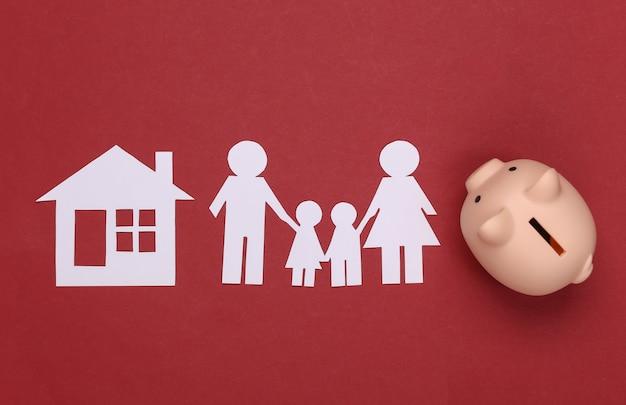 Papier gelukkige familie samen met huis en spaarvarken op rood. gezinsbudget