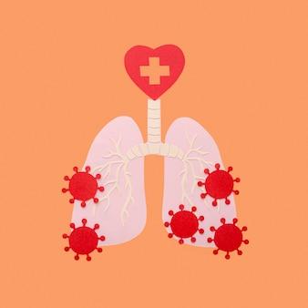 Papier gemaakt longen geïsoleerd op oranje met virussen