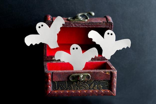 Papier gesneden enge spoken vliegen uit een oude vintage houten kist