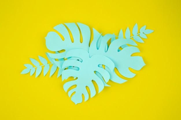 Papier gesneden stijl van monsterabladeren op gele achtergrond