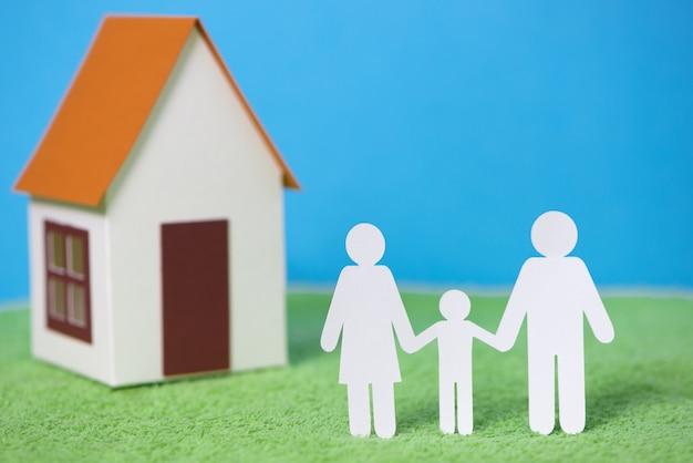 Papier gesneden van familie met huis op groen gras achtergrond
