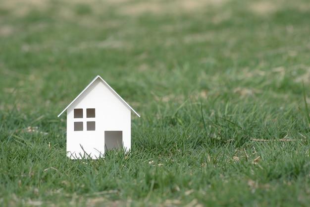 Papier gesneden van huis op gras met kopie ruimte.
