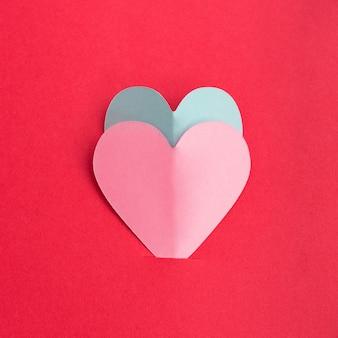 Papier gesneden van roze en blauwe harten op rode achtergrond. valentijnsdag concept. plat leggen