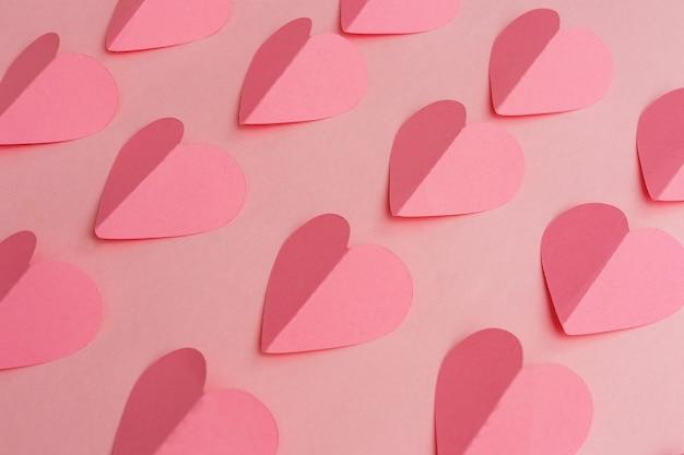 Papier gesneden van roze harten op roze achtergrond