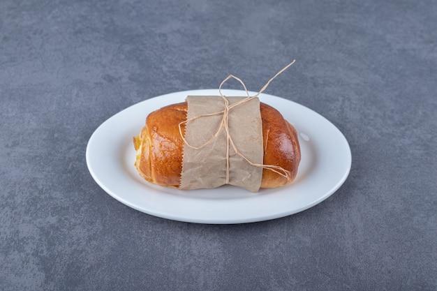 Papier gewikkeld zoet brood op plaat op marmeren tafel.