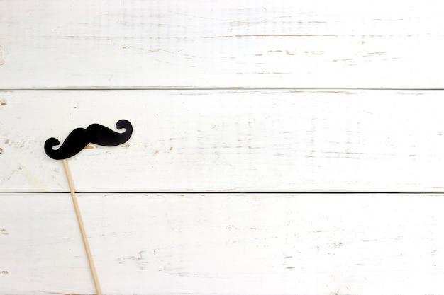 Papier hart vorm nep snorren op witte houten achtergrond.