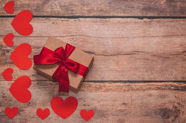 Papier harten en een ambachtelijke aanwezig met rood lint op een houten achtergrond. bovenaanzicht, plat liggend. valentijnsdag concept. copyspace.
