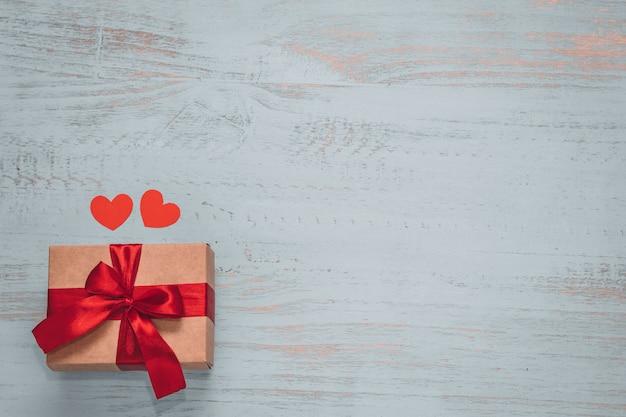 Papier harten en een ambachtelijke aanwezig met rood lint op een licht geschilderde houten achtergrond. bovenaanzicht, plat liggend. valentijnsdag concept. copyspace.