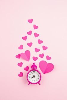 Papier harten en wekker over de roze pastel achtergrond.