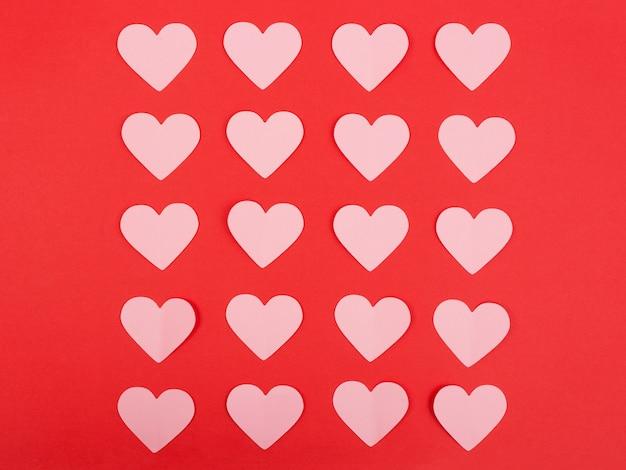 Papier harten gerangschikt in rijen op roze achtergrond. uitzicht van boven