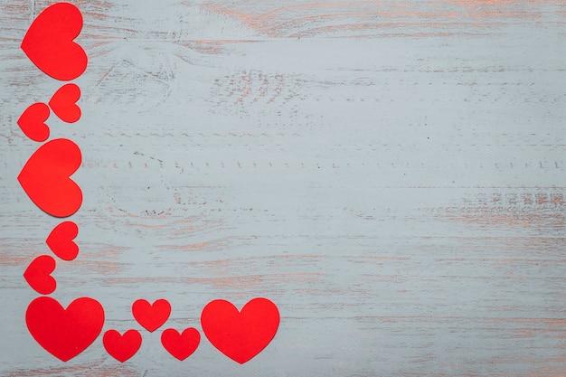 Papier hartjes op een licht geschilderde houten achtergrond. bovenaanzicht, plat liggend. valentijnsdag concept. copyspace. ornament.