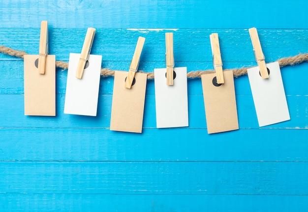 Papier hechten aan touw met kleren pinnen op houten achtergrond