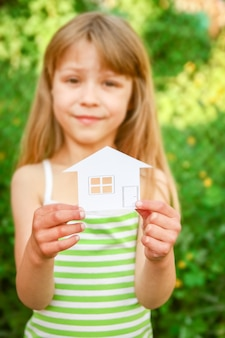 Papier huis in handen op een achtergrond van onroerend goed