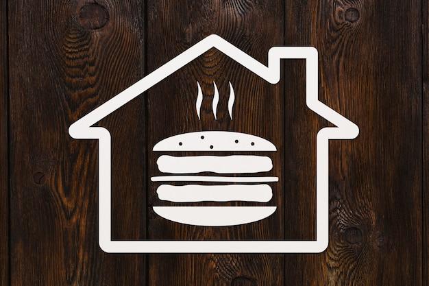 Papier huis met hamburger binnen op houten achtergrond, fast-food concept