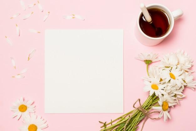Papier in de buurt van bloemen en een kopje drank