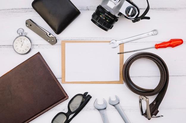 Papier in de buurt van camera, notebook, stopwatch, reparatiemateriaal en leren riem
