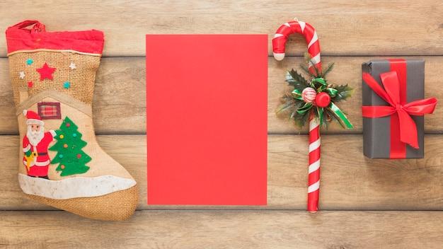 Papier in de buurt van kerstsok, wandelstok en geschenkdoos