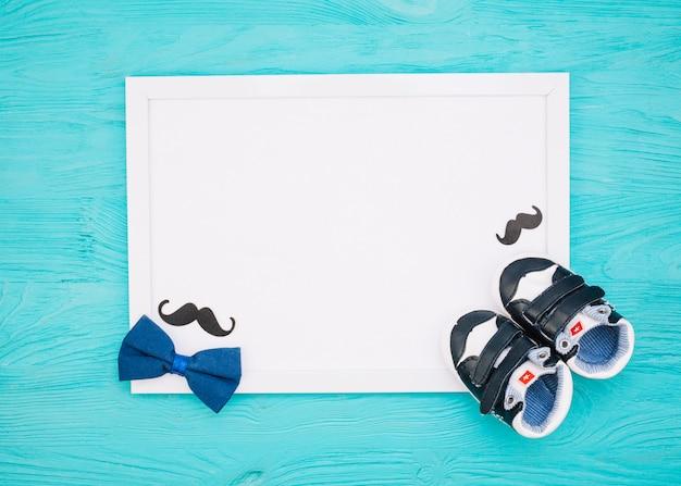 Papier in de buurt van snor, vlinderdas en kinderschoenen