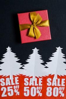 Papier kerstbomen met rode kortingskaarten en een geschenk