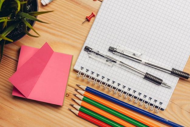 Papier kleurpotloden schaar briefpapier schoolbank.
