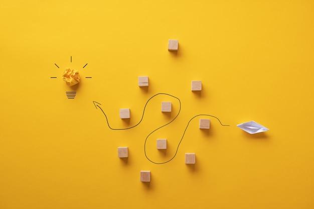 Papier maakte origami-boot die door metaforische obstakels vaart om het doel een idee te bereiken.