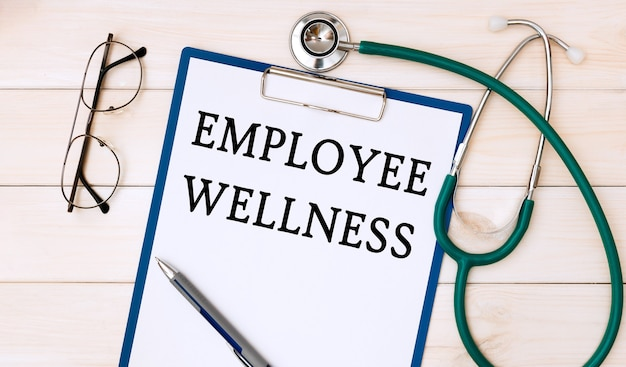 Papier met employee wellness op het bureau, stethoscoop en bril