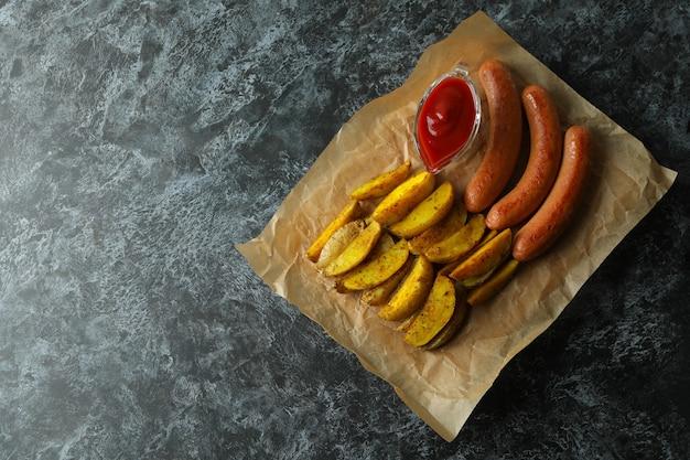 Papier met gebakken aardappel, saus en worst op zwarte smokey achtergrond