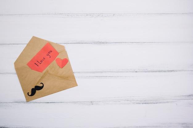 Papier met ik hou van je titel in de buurt van het hart en decoratieve snor op brief