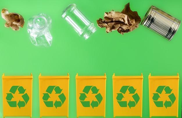 Papier, metaal, glas, plastic, organisch afval in verschillende gele containers op een lichtgroene achtergrond gooien. afvalscheiding en recyclingconcept