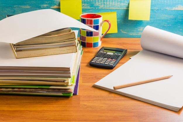Papier, notitieboeken, boeken op het bureau. tijd doorgebracht aan een heel lange tafel.