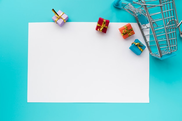 Papier omringd met mini-cadeautjes en winkelwagentjes